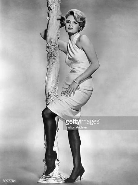 Fulllength studio portrait of American actor Angie Dickinson leaning on a decorated pole She is wearing a lightcolored halter dress with dark...