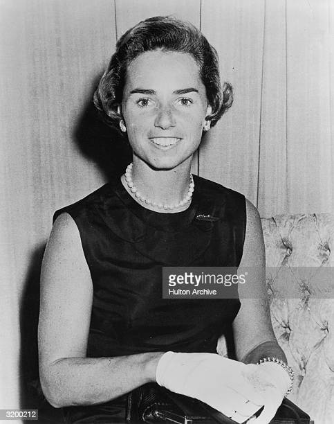 Portrait of Ethel Kennedy the wife of Robert Kennedy sitting in a black dress pearl necklace and white gloves
