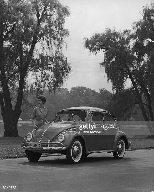 Promotional image of a woman standing next to a 1962 Volkswagen Beetle Sedan in a park with a lake