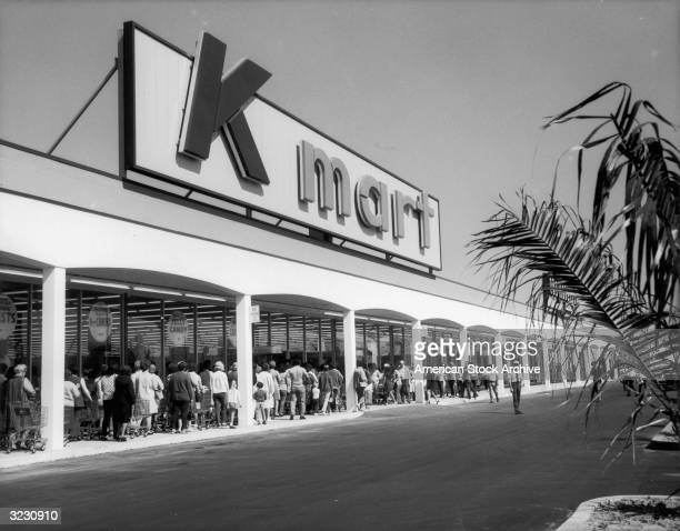 A huge line of people with shopping carts wait to enter the Kmart shopping center