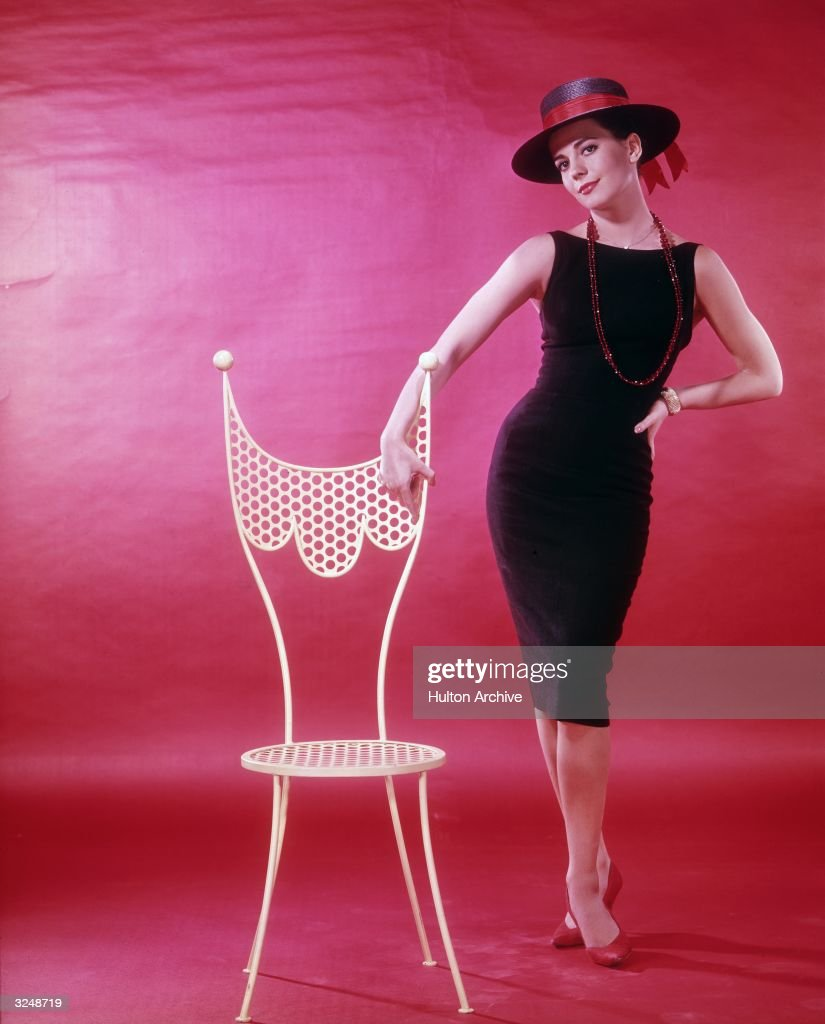 American actor Natalie Wood (1938 - 1981) wearing a sleeveless black dress, red beaded necklace and a wide-brimmed black hat, posing next to a white chair.
