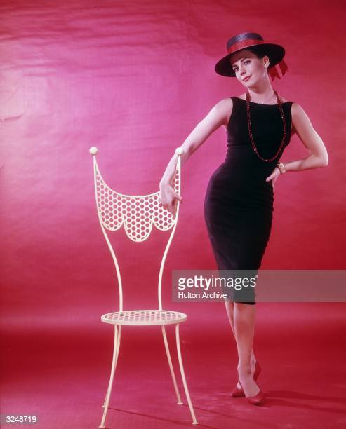 American actor Natalie Wood wearing a sleeveless black dress, red beaded necklace and a wide-brimmed black hat, posing next to a white chair.