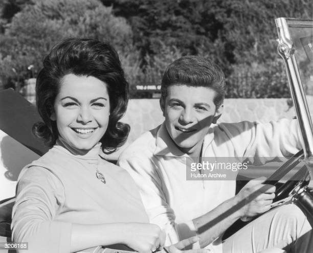 American actors and singers Annette Funicello and Frankie Avalon smile from the front seat of a convertible The two starred in many 'beach' movies...