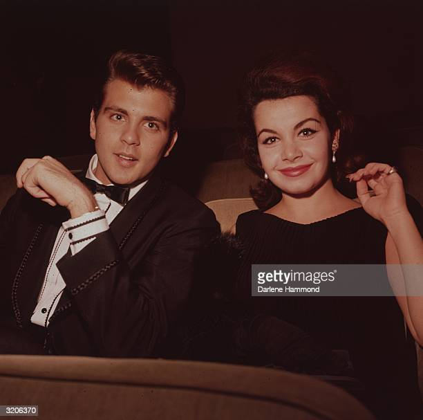 American vocalist Fabian and American actor and Mickey Mouseketeer Annette Funicello sit in a theater Funicello wears a black dress and Fabian wears...
