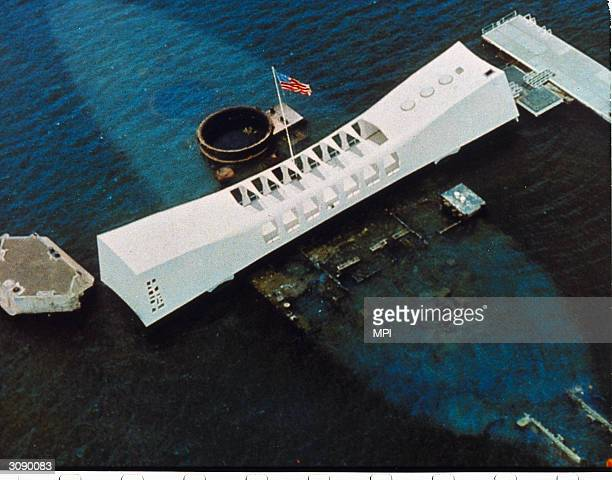 An aerial view of the USS Arizona National Memorial which spans the sunken hull of the battleship in Pearl Harbor Oahu Hawaii and commemorates the...