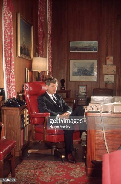 Attorney General Robert F Kennedy sits at his desk with his hands folded on his lap