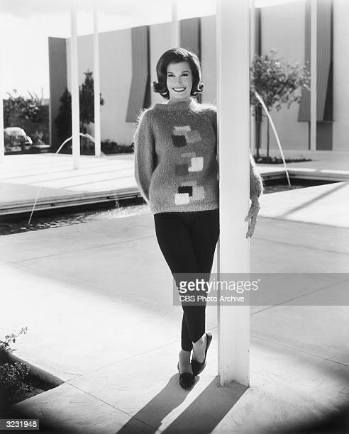 Fulllength portrait of American actress Mary Tyler Moore standing outdoors on a patio near two fountains wearing a sweater and capri pants