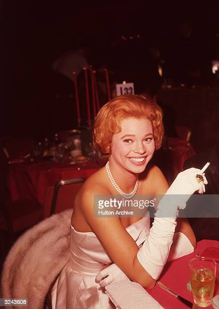 Indianborn actress Juliet Prowse smiles as she smokes a cigarette while sitting at a dinner table next to an unidentified man early 1960s Prowse is...