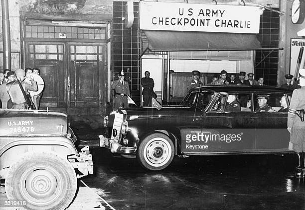 Military personnel in a car pass through the US Army's Checkpoint Charlie on the Berlin Wall