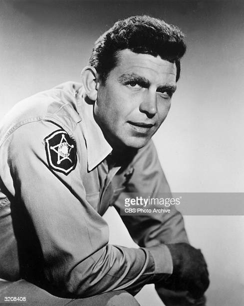Portrait of American actor Andy Griffith leaning forward and wearing his sheriff's costume from the television series, 'The Andy Griffith Show'.