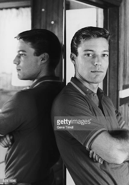 Portrait of American actor Richard Chamberlain leaning against a wall mirror wearing a shortsleeved polo shirt