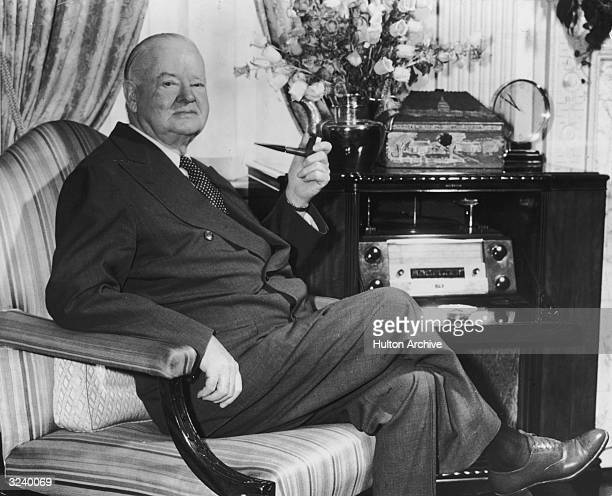 Portrait of former American president Herbert Hoover seated in an armchair with a pipe in his suite at the Waldorf Towers, New York City.