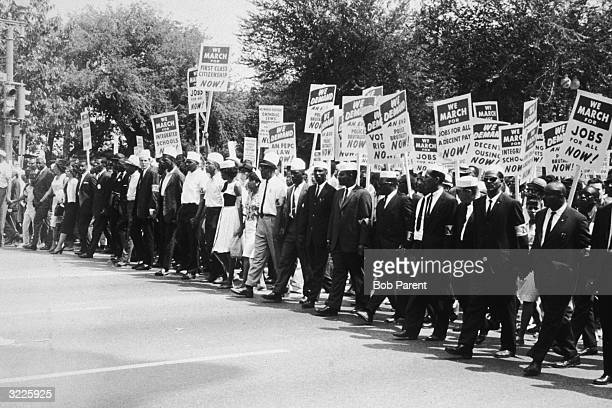 Rows of AfricanAmerican people wearing white caps and arm bands printed with the letter 'M' marching with placards in a civil rights demonstration...