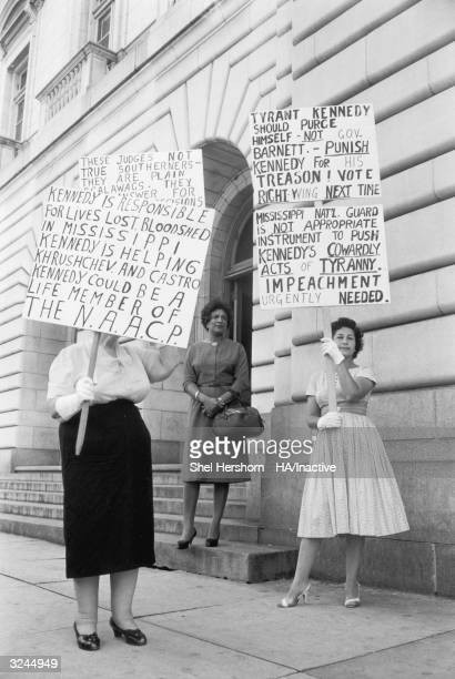 Two white women hold up signs protesting desegregation and Kennedy outside of a meeting of the National Association for the Advancement of Colored...