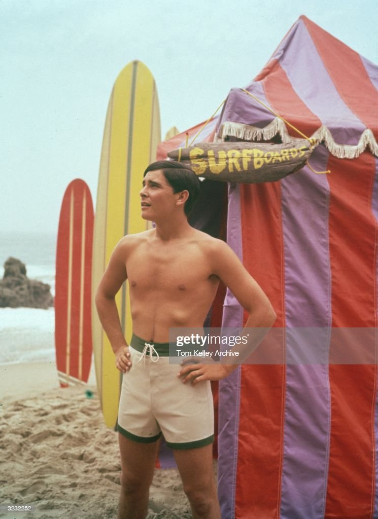 A man wearing swimming trunks standing outside a beach hut with a sign that says, 'Surfboards', with two surfboards sticking out of the sand in the background.