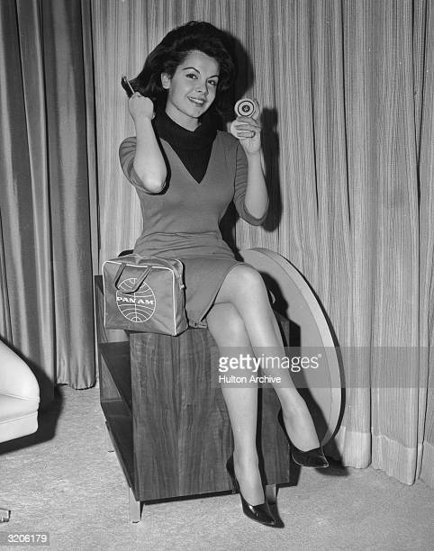 American actor and singer Annette Funicello smiles and brushes her hair using a compact prior to embarking on a European publicity tour for director...