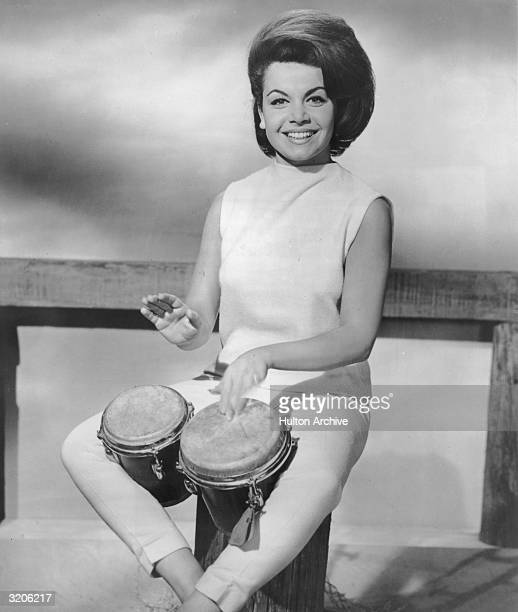 American actor and singer Annette Funicello smiles while playing bongos on a wooden post in a promotional portrait Funicello has a bouffant and wears...