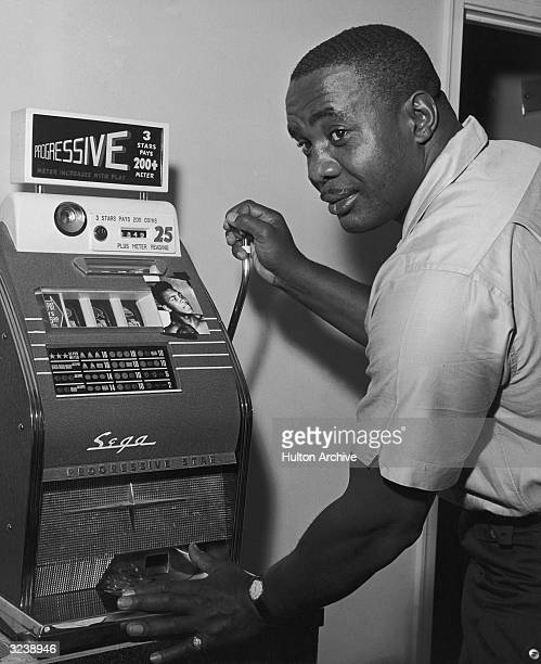 American heavyweight champion boxer Sonny Liston looks over his shoulder while pulling the handle of a slot machine to which a small photograph of...