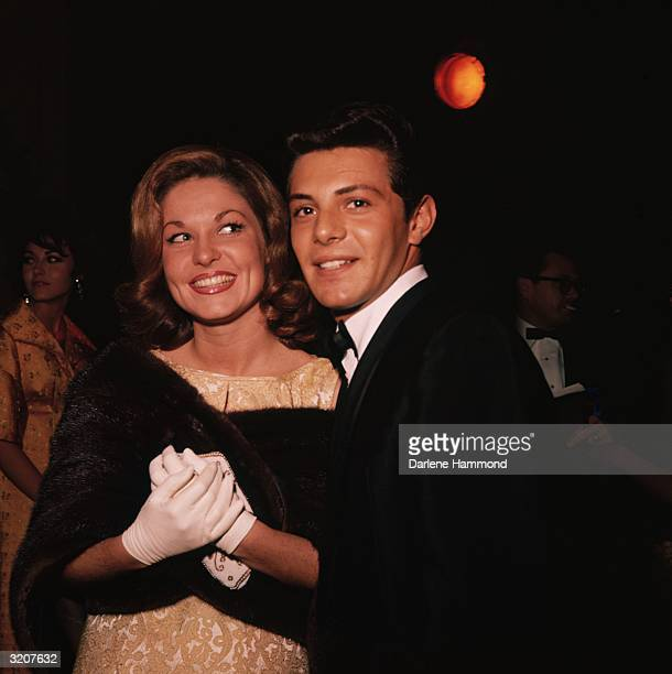 American singer and actor Frankie Avalon smiles as he poses with his wife Kay Dible She wears a fur wrap and holds her purse