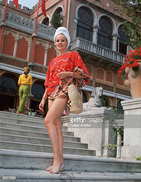 Fulllength image of American actor Carroll Baker posing outdoors on a flight of steps next to a miniature concrete sphinx She wears her hair in a...