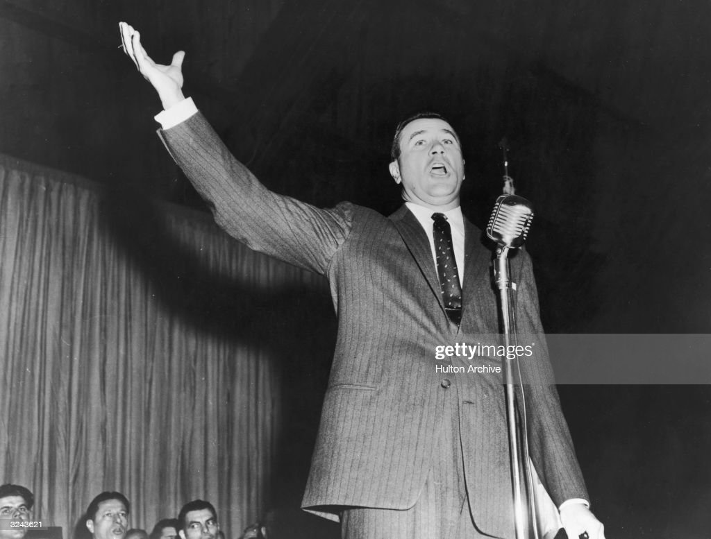 Low-angle image of American evangelist Oral Roberts holding his hand in the air and preaching while standing behind a microphone on stage.