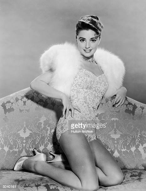 Studio portrait of Italianborn actor and singer Anna Maria Alberghetti posing on a sofa in a lace slip a fur wrap and satin pumps