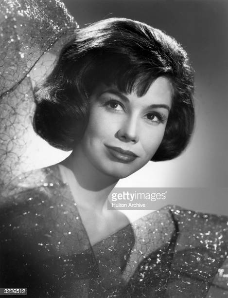 American actor Mary Tyler Moore smiles while surrounded by netting in a promotional portrait for the television series, 'The Dick Van Dyke Show'.