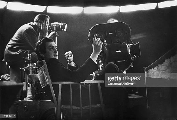 American film director Stanley Kubrick sits near a movie camera on the set of his film 'Dr Strangelove or How I Learned to Stop Worrying and Love the...
