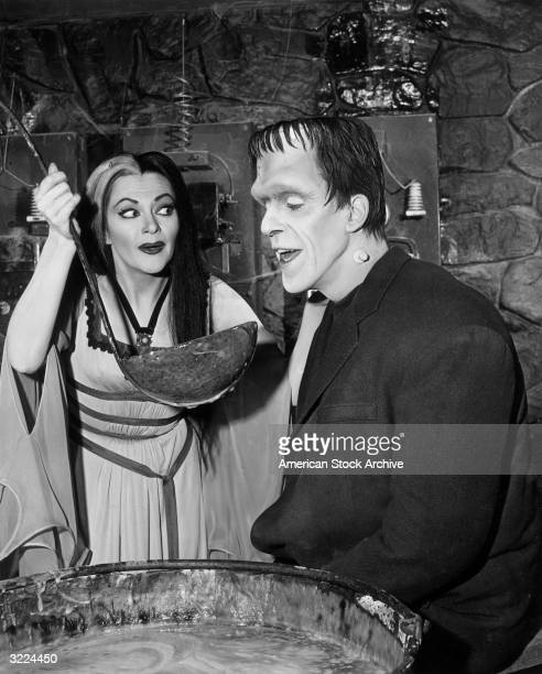 Canadian actor Yvonne De Carlo as Lily Munster holds a giant ladle for American actor Fred Gwynne as Herman Munster in a still from the television...