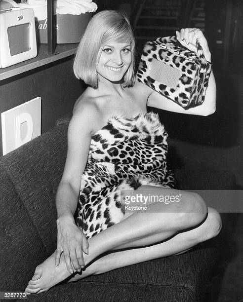 Louise Cigarini wearing a leopardskin outfit holds up the new leopardskin Roberts Radio 500 at the press preview of the 1964 TV and Radio Show at...