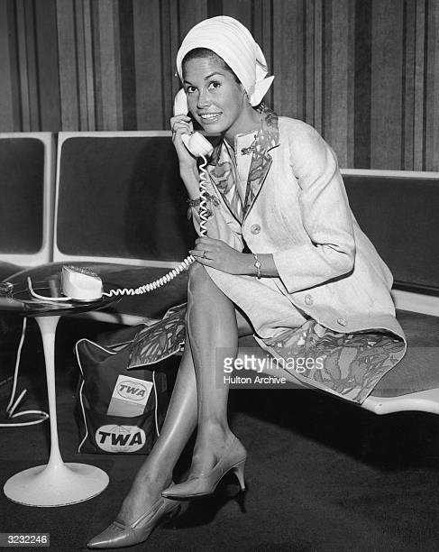 Portrait of American actor Mary Tyler Moore holding a telephone up to her ear and smiling at Kennedy International Airport, New York City,. She wears...