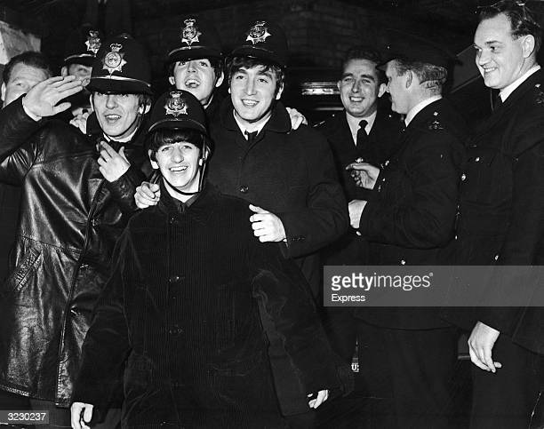The British rock group The Beatles clown in bobby helmets next to uniformed bobbies Birmingham England Clockwise from L George Harrison saluting Paul...