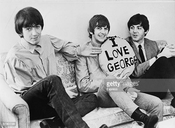 Three of the four members of the British rock group The Beatles sit on a sofa LR George Harrison Ringo Starr and Paul McCartney Starr holds a pillow...