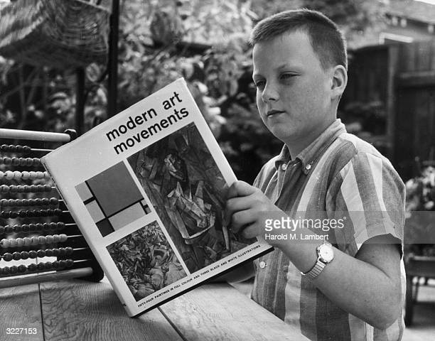 A boy sits at an outdoor picnic table reading a book entitled 'Modern Art Movements' There is an abacus on the table beside him