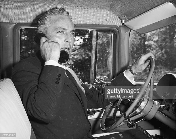 A businessman sits in the driver's seat of an automobile speaking on a telephone with one hand on the steering wheel