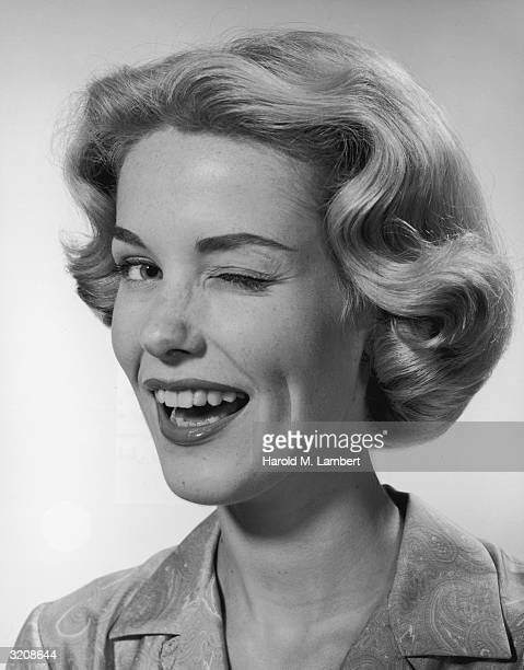 A headshot of a blonde woman winking