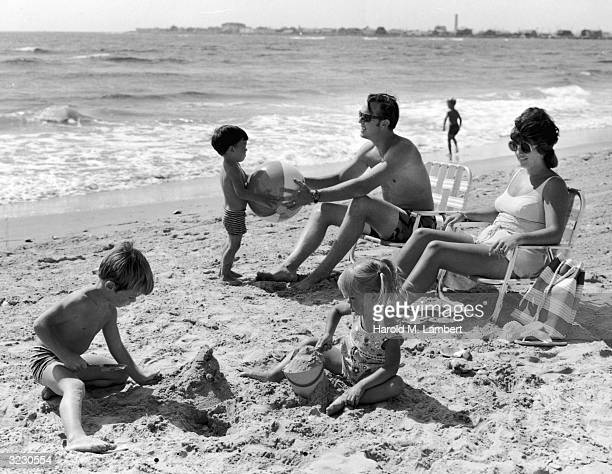 A husband and wife sit on lawn chairs on a beach watching their sons play in the sand One of the boys hands a beach ball to his father The other...
