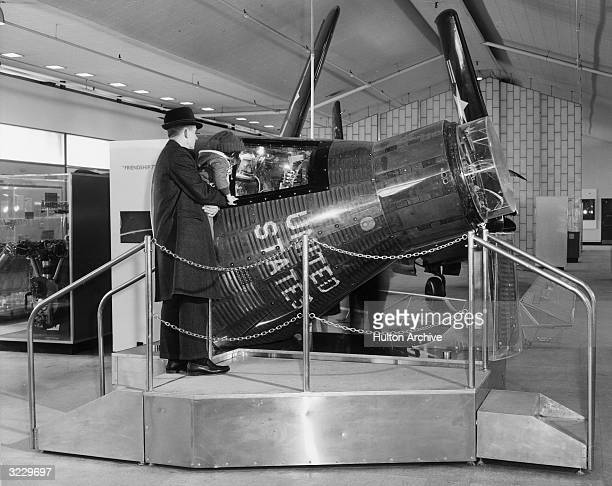 A man holds up his small daughter to look at an exhibit of the Friendship 7 space capsule 1960s Friendship 7 was used in some of the first manned...