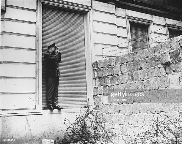 A military officer looking over the Berlin Wall at Bernauer Strasse in West Berlin
