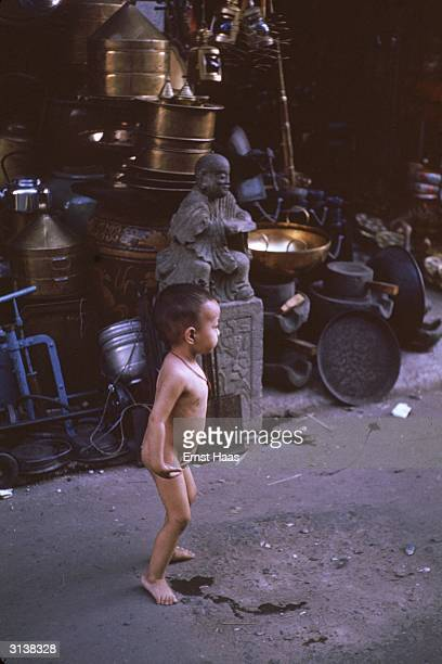 A naked child urinating in front of a bricabrac store in Indochina