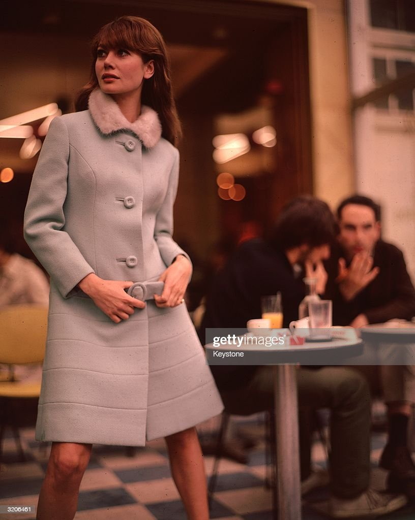 A sixties fashion model wearing a classic winter coat belted at the waist and with a knee-length hemline.