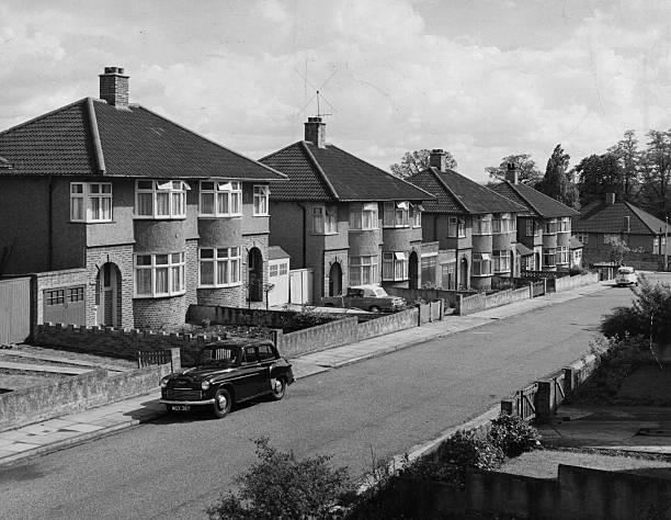A suburban street with rows of semi-detached houses....