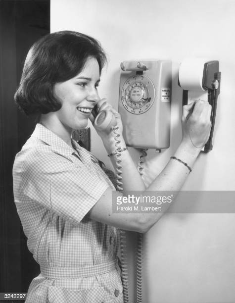 A woman in a gingham dress talks on a rotary telephone and smiles as she takes notes on a pad of paper affixed to the wall