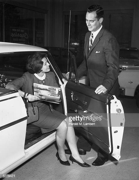 Woman points to a catalogue while she and her husband inspect an automobile in a car showroom.