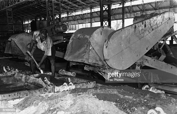 A worker mixes tin ore with limestone and anthracite in readiness for smelting at Straits Trading Smelting Works Butterworth Malaysia