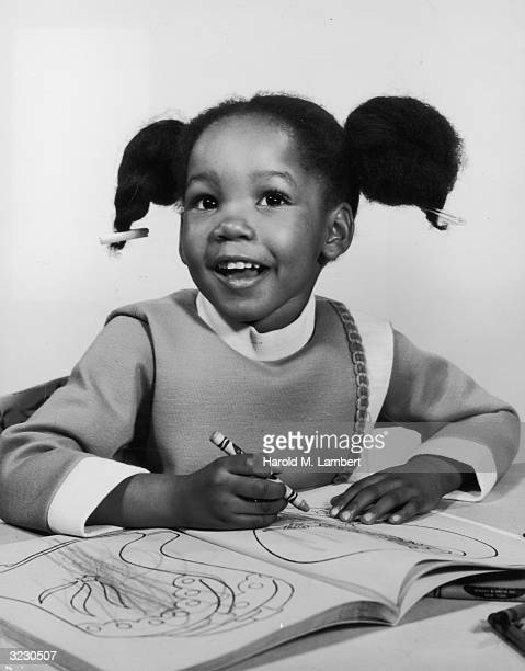 A young AfricanAmerican girl looks up and smiles as she sits and colors with a crayon in a coloring book She wears her hair in pigtails