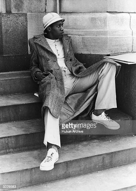 A young AfricanAmerican man reclines on the front steps of a building in a cap a herringbone overcoat and canvas sneakers