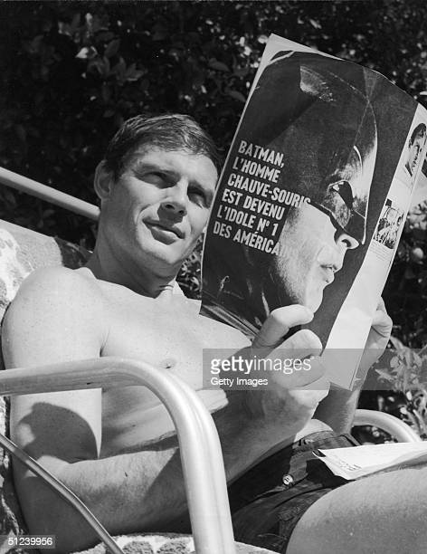 Circa 1965 American actor Adam West from the television series 'Batman' sits in a beach chair at his home reading a French magazine about the series...