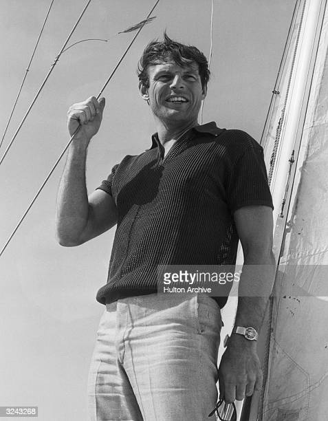 American actor Adam West of the television series 'Batman' stands outdoors on a sailboat holding a mast line with the wind blowing his hair