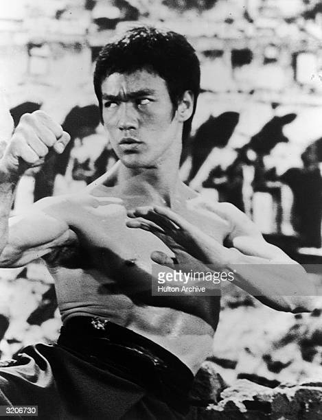 American actor and martial artist Bruce Lee raises his hands in a defensive stance during a fight in an unidentified film still
